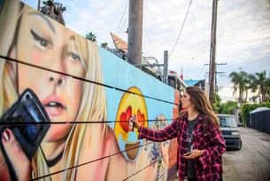 Graffiti artist spray painting wall on street, Venice Beach, California, USAの写真素材 [FYI03803860]