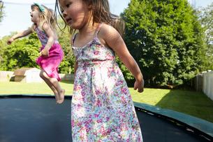 Two girls jumping on trampoline in gardenの写真素材 [FYI03803869]