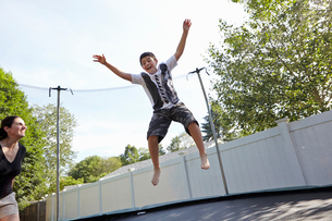 Mother watches son jumping on trampoline in gardenの写真素材 [FYI03803870]