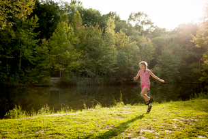 Girl skipping along river bank arms openの写真素材 [FYI03803897]