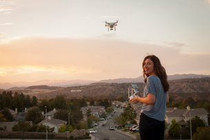 Female commercial operator flying drone above housing development, looking over shoulder at camera,の写真素材 [FYI03803951]