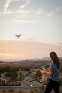 Female commercial operator flying drone above housing development, Santa Clarita, California, USAの写真素材 [FYI03803952]