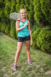 Teenager with tennis racket in gardenの写真素材 [FYI03803965]