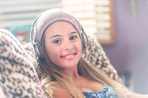 Teenager with earphones smiling on lazy chairの写真素材 [FYI03803967]