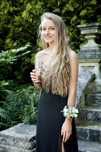 Teenage girl wearing prom dress and corsage holding champagne flute looking at camera smilingの写真素材 [FYI03803982]