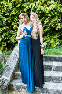 Teenage girls wearing prom dresses holding champagne flute looking at camera smilingの写真素材 [FYI03803989]