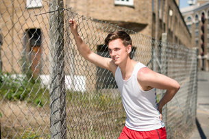 Runner stretching against wire fence, Wapping, Londonの写真素材 [FYI03804054]