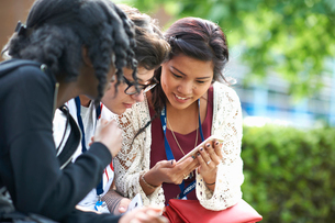 Female students on college campus reading smartphone textsの写真素材 [FYI03804086]