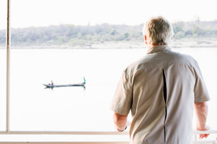 Senior man on safari looking out at river, Kafue National Park, Zambiaの写真素材 [FYI03804129]