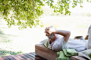 Senior man relaxing on daybed at safari lodge, Kafue National Park, Zambiaの写真素材 [FYI03804139]