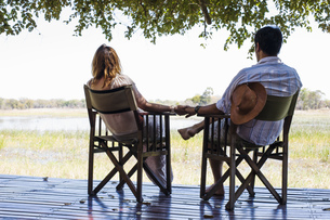 Romantic couple holding hands whilst sitting  at safari lodge, Kafue National Park, Zambiaの写真素材 [FYI03804140]