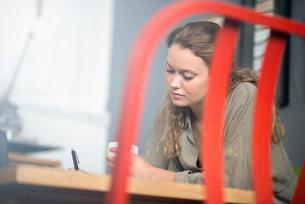 Female print designer working at desk in workshopの写真素材 [FYI03804160]