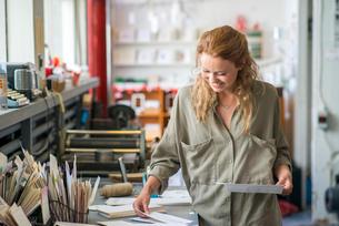 Female print designer examining designs in workshopの写真素材 [FYI03804161]