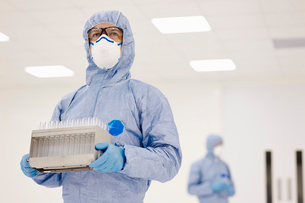 Scientist carrying tray of test tubes in laboratoryの写真素材 [FYI03804206]