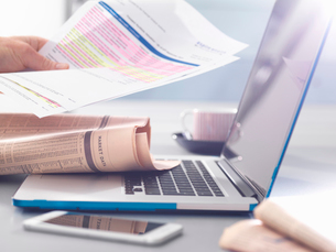 Man reviewing financial affairs using newspaper market data, investment statement and laptopの写真素材 [FYI03804234]
