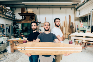 Friends standing in carpentry workshop holding skateboard looking at cameraの写真素材 [FYI03804243]