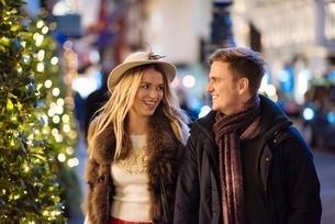Romantic young couple strolling along New Bond street at xmas, London, UKの写真素材 [FYI03804320]