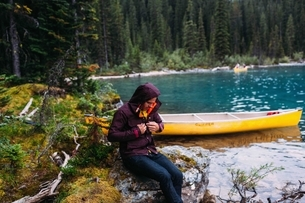 Mid adult man sitting by canoe on Moraine lake, looking down fastening waterproof coat, Banff Nationの写真素材 [FYI03804395]