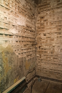 Partially demolished plaster and wooden lattice walls in a room inside an old 1800s cottage style hoの写真素材 [FYI03804408]