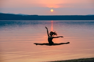 Side view of girl by ocean at sunset leaping in mid air, arms raised doing the splitsの写真素材 [FYI03804429]