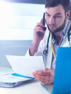 Junior doctor using smartphone whilst reading medical records in clinicの写真素材 [FYI03804445]
