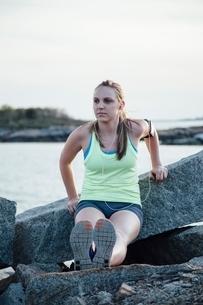 Woman doing reverse push up on rock looking awayの写真素材 [FYI03804501]