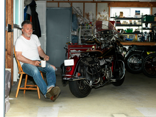 Senior man sitting with a coffee in garage with motorcycleの写真素材 [FYI03804655]