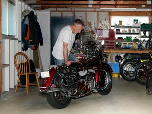 Senior man checking over motorcycle in garageの写真素材 [FYI03804661]
