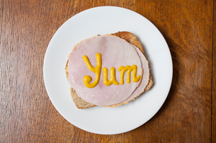 Overhead view of the word yum written on ham on toast in mustardの写真素材 [FYI03804683]