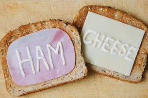 Overhead view of the words ham and cheese written on toast in mayonnaiseの写真素材 [FYI03804690]