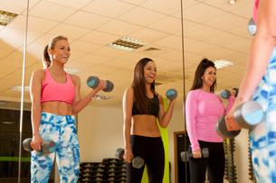 Mirror image of women in gym using dumbbellsの写真素材 [FYI03804692]