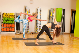 Woman on yoga mat in gym doing stretching exercisesの写真素材 [FYI03804698]