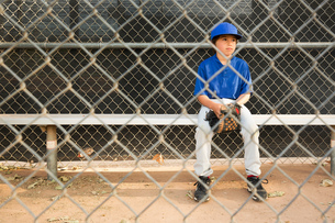 Boy sitting on bench behind wire fence at baseball practiseの写真素材 [FYI03804708]