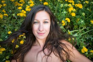 Woman lying on field of wildflowersの写真素材 [FYI03804838]