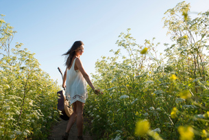 Woman with guitar in field of wildflowersの写真素材 [FYI03804847]