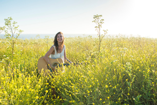 Woman with guitar in field of wildflowersの写真素材 [FYI03804850]