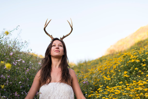 Woman putting on horns in field of wildflowersの写真素材 [FYI03804851]