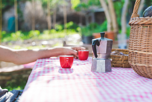 Man's hand with espresso cup at table in gardenの写真素材 [FYI03804898]