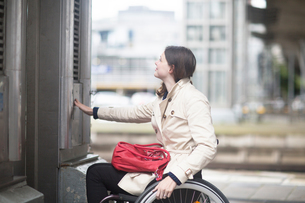 Young woman using wheelchair pressing control for city elevatorの写真素材 [FYI03804903]