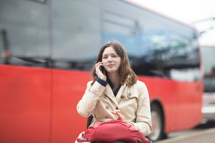 Young woman using wheelchair talking on smartphone at city bus stationの写真素材 [FYI03804910]