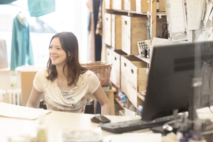 Young female shop assistant using wheelchair behind shop checkoutの写真素材 [FYI03804912]