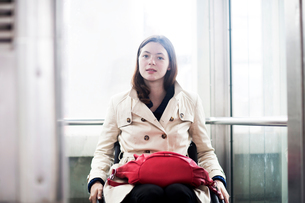 Portrait of young woman using wheelchair in elevatorの写真素材 [FYI03804914]