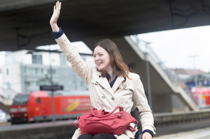 Young woman using wheelchair waving from city train stationの写真素材 [FYI03804915]