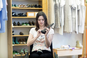 Young woman using wheelchair looking at shoes in shopの写真素材 [FYI03804916]