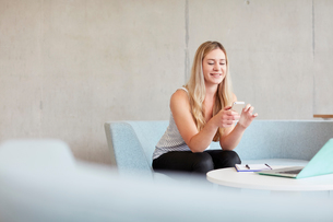 Young female student sitting on study space sofa reading smartphone texts at higher education collegの写真素材 [FYI03804930]