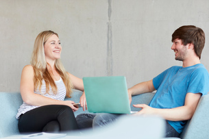 Young male and female students sitting on study space sofa using laptop at higher education collegeの写真素材 [FYI03804938]