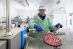 Worker making Italian sausages in sausage factoryの写真素材 [FYI03804972]
