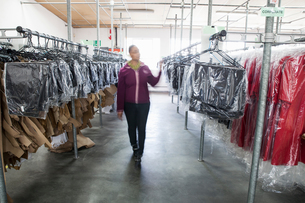 Woman between clothes rail in sewing factory sample roomの写真素材 [FYI03804984]