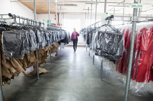 Woman between clothes rail in sewing factory sample roomの写真素材 [FYI03804994]