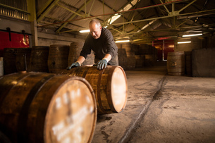 Worker rolling whisky cask in whisky distillery warehouseの写真素材 [FYI03804997]